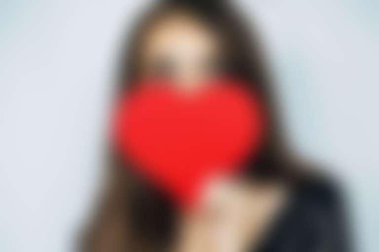 Девушка закрывает нижнюю часть лица красным сердечком