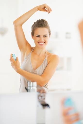Женщина наносит дезодорант