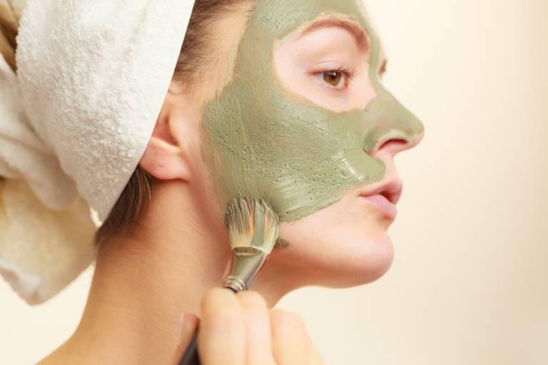 Женщина наносит глиняную маску на лицо