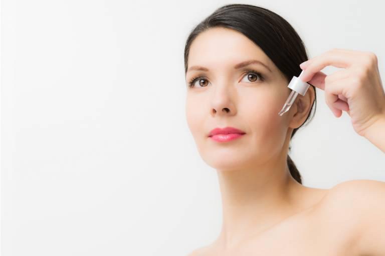 Женщина применяет сыворотку для лица