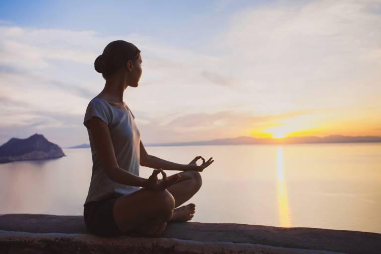 Женщина в медитации на берегу моря