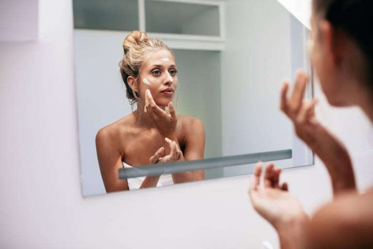 Женщина наносит крем на лицо