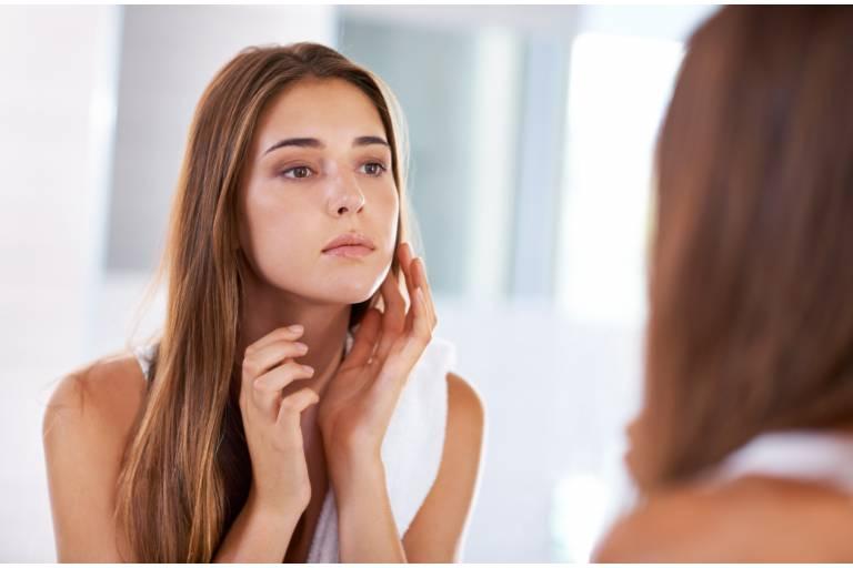 Женщина изучает своё лицо