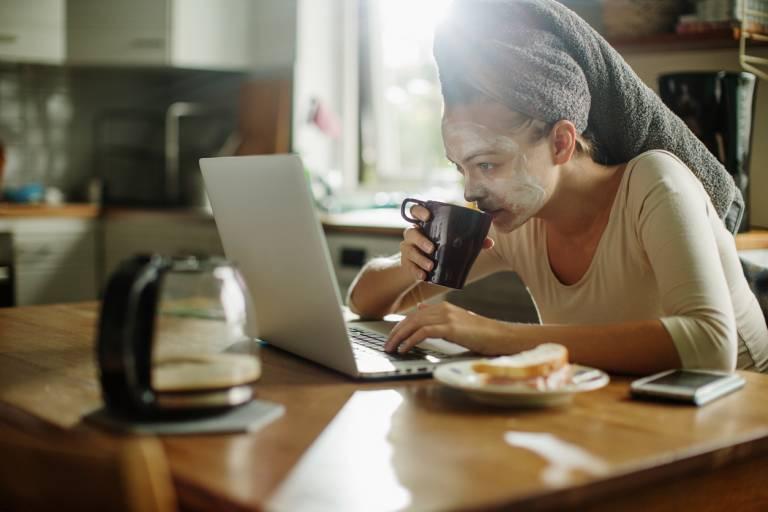 Женщина с маской на лице за завтраком