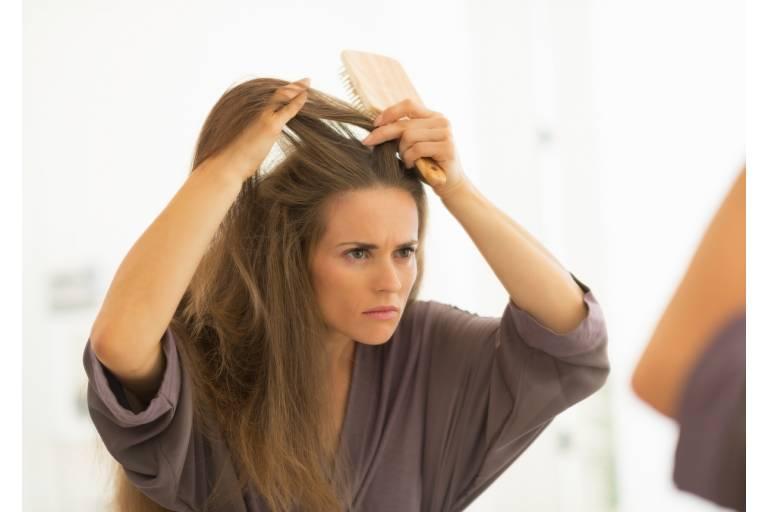 Женщина разглядывает свои волосы