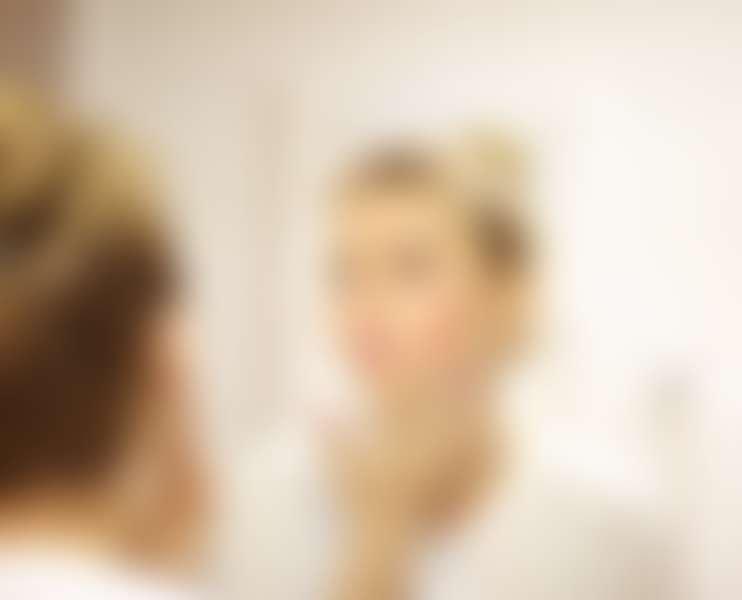 Девушка наносит на кожу крем с пантенолом