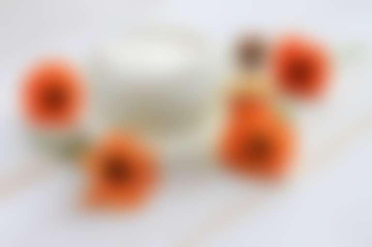 На белом фоне открытая баночка с кремом, вокруг нее цветки календулы