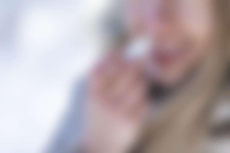 Девушка наносит бальзам с маслом макадамии на губы