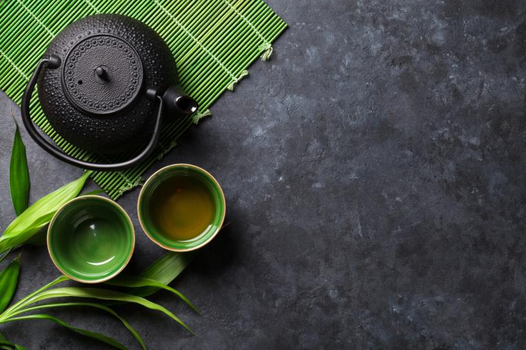 Черный чайник и пиалы с зеленым чаем