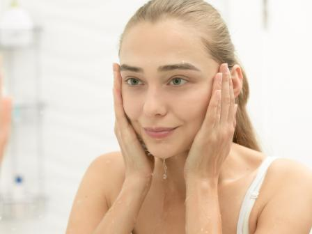Блондинка смотрит в зеркало после очищения кожи