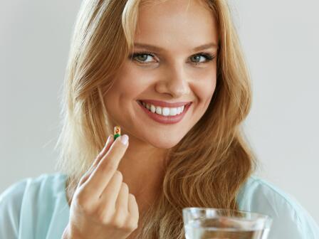 девушка держит в руке витамин