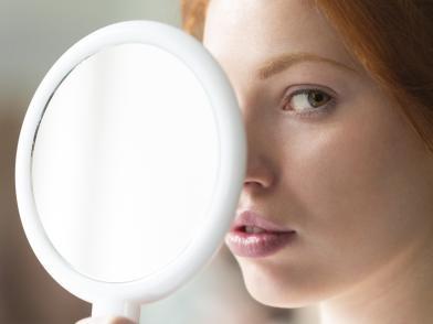 девушка смотрит в увеличительное зеркало