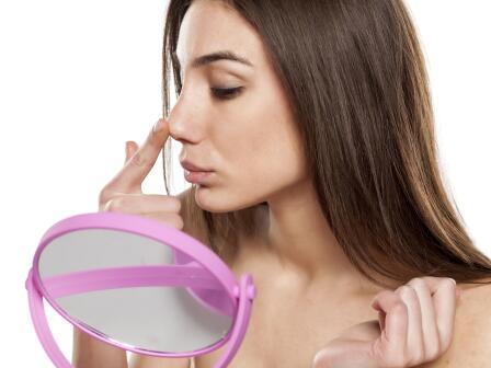 девушка смотрит в зеркало на прыщи на носу