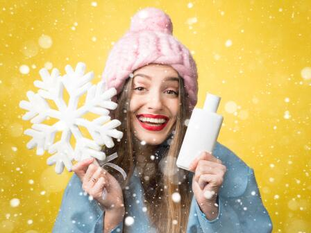Девушка в зимней шапке держит крем для лица