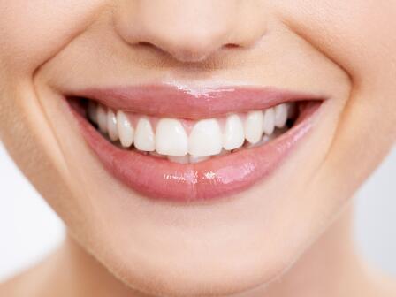 нижняя половина женского лица улыбка с белоснежными зубами и влажными блестящими губами