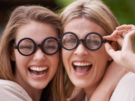 девушка и женщина с ухоженной хорошей кожей, в круглых очках с черными оправами смеются