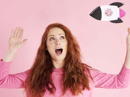 на розовом фоне девушка с пышными рыжими волосами в розовой майке смотрит на игрушечную ракету