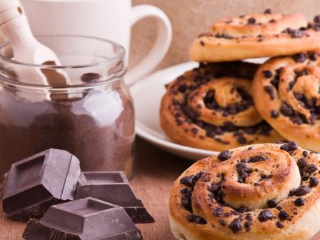 на столе кубики шоколада, банка какао, булочки с шоколадными каплями в белой тарелке, еда. вредная для кожи