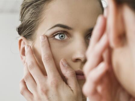 темноволосая девушка внимательно смотрит в зеркало и трогает кожу в области век