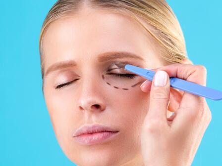 на голубом фоне девушке с закрытыми глазами намечают черным пунктиром контуры вокруг глаза