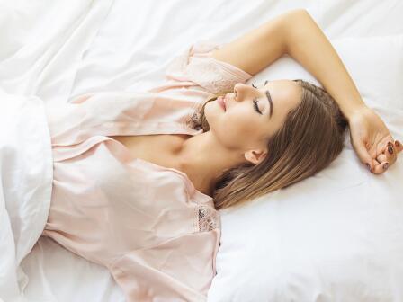 на белой постели спит светловолосая девушка с красивой кожей, в бледно-розовом пеньюаре