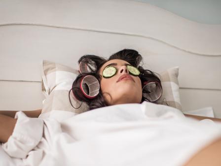 Девушка в бегуди лежит на кровати