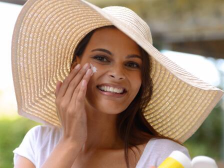 Смуглая девушка в шляпе намазывает лицо солнцезащитным кремом