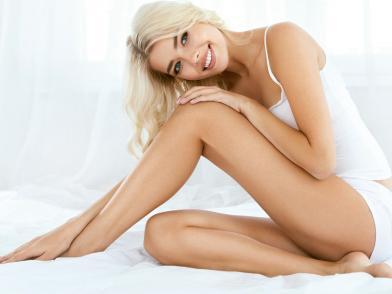 Блондинка в белой майке и трусиках сидит в кокетливой позе на белой кровати на белом фоне и смотрит в кадр