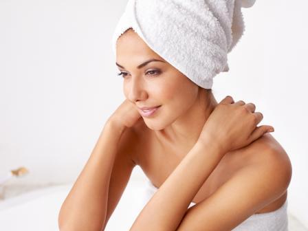 Девушка с белым полотенцем на голове держит себя за плечи и смотрит вниз и вбок