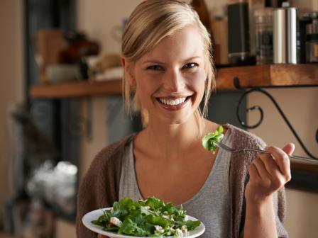 Девушка держит в руках тарелку с салатом и, улыбаясь, смотрит в кадр