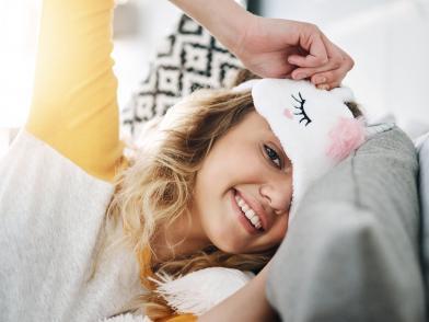 Улыбающаяся девушка в кровати, выглядывающая из-под маски для сна