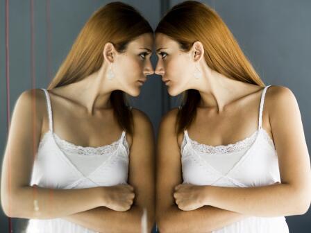 Девушка в белом сарафане стоит у зеркала, прислонившись к нему лбом.