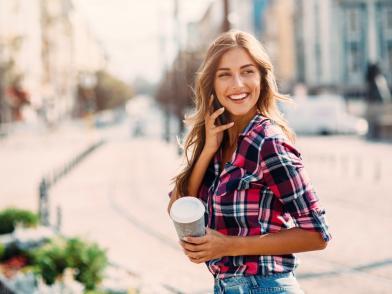 Улыбающаяся блондинка в клетчатой рубашке в летнем городе говорит по мобильному
