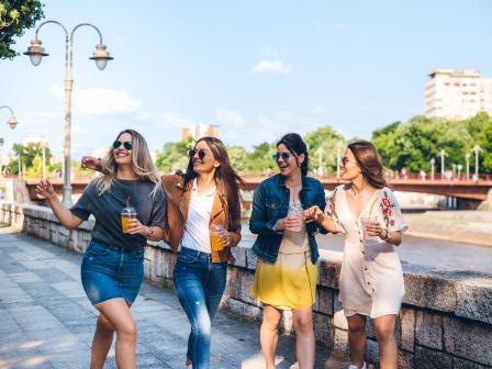 Четыре девушки весело шагают по набережной летнего города