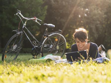 Девушка с радостным лицом лежит на траве рядом с припаркованным велосипедом и  смотрит в планшет