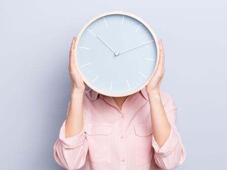 Девушка в розовой сорочке держит в руках настенным часы, закрывая ими лицо