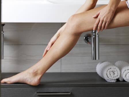 Кудрявая девушка в ванной наносит на ногу крем