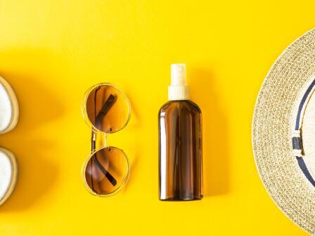 Коричневая бутылочка-спрей, солнечные очки, сандали и соломенная шляпа - на оранжевом фоне