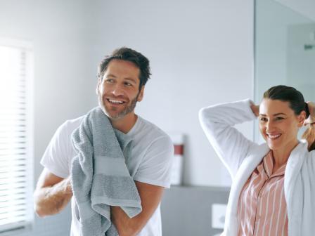 Мужчина после душа промокает бороду полотенцем