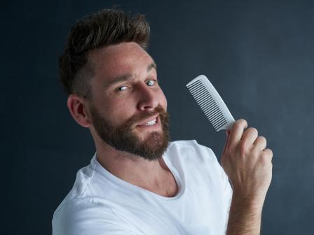 Мужчина собирается расчесать бороду