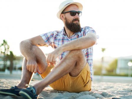 Мужчина с бородой сидит на песке