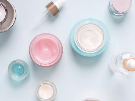 Открытые круглые баночки с косметическими кремами разного цвета, снятые сверху