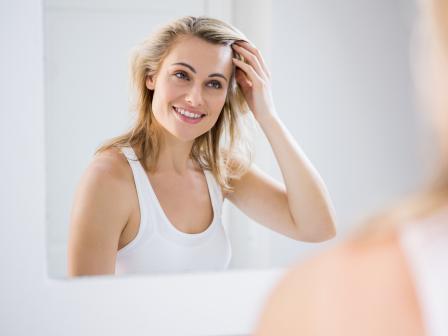 Улыбающаяся блондинка в белой майке смотрит на свое отражение в зеркале