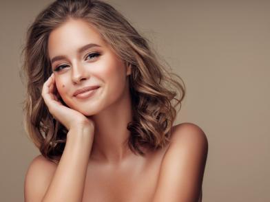 Улыбающаяся девушка с золотистой сияющей кожей