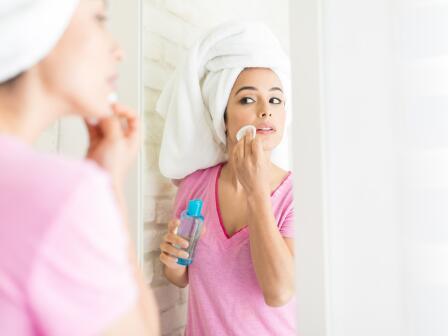 Девушка в розовой футболке с тюрбаном из полотенца на голове протирает лицо тоником