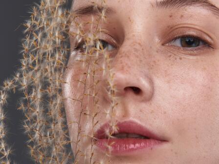 Девушка с веснушками и пушистым растением у лица
