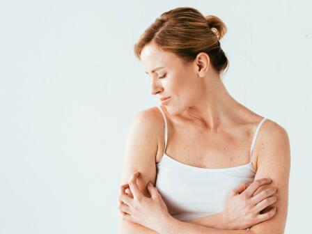 женщина в белом топике чешет руки из-за зуда кожи