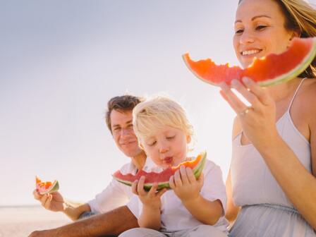 счастливая семья на пляже ест арбуз, богатый пребиотиками