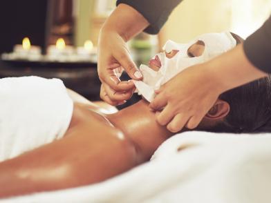 Девушка лежит в кабинете косметолога с тканевой маской для лица