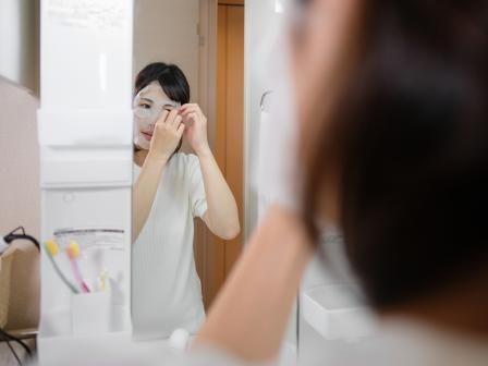 Девушка-азиатка накладывает на лицо тканевую маску.